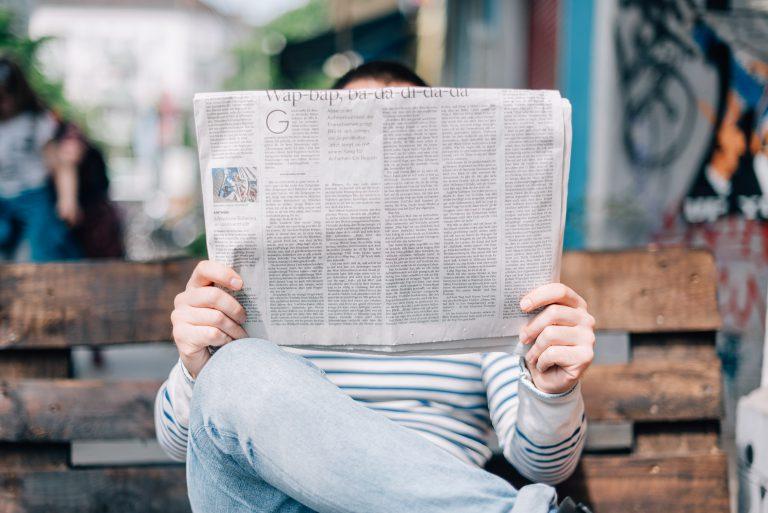 Homme lisant son journal assis sur un banc
